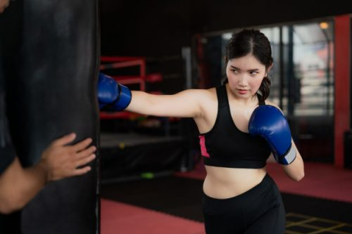 portrait-asian-confident-young-boxer-woman-with-blue-boxing-gloves-punching-bag-with-trainer-professioal-gym-sporty-fit-healthy-lifestyle-asian-model-boxing-gym-concept_73503-1503